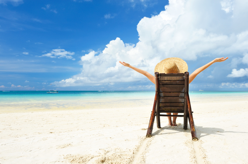 Hawaii Eco Resorts: Woman sitting in a beach chair over looking ocean in Hawaii